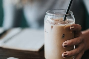 Woman holding jar with infused iced coffee in it with a black straw on a brown wooden table with notepad and iphone beside it