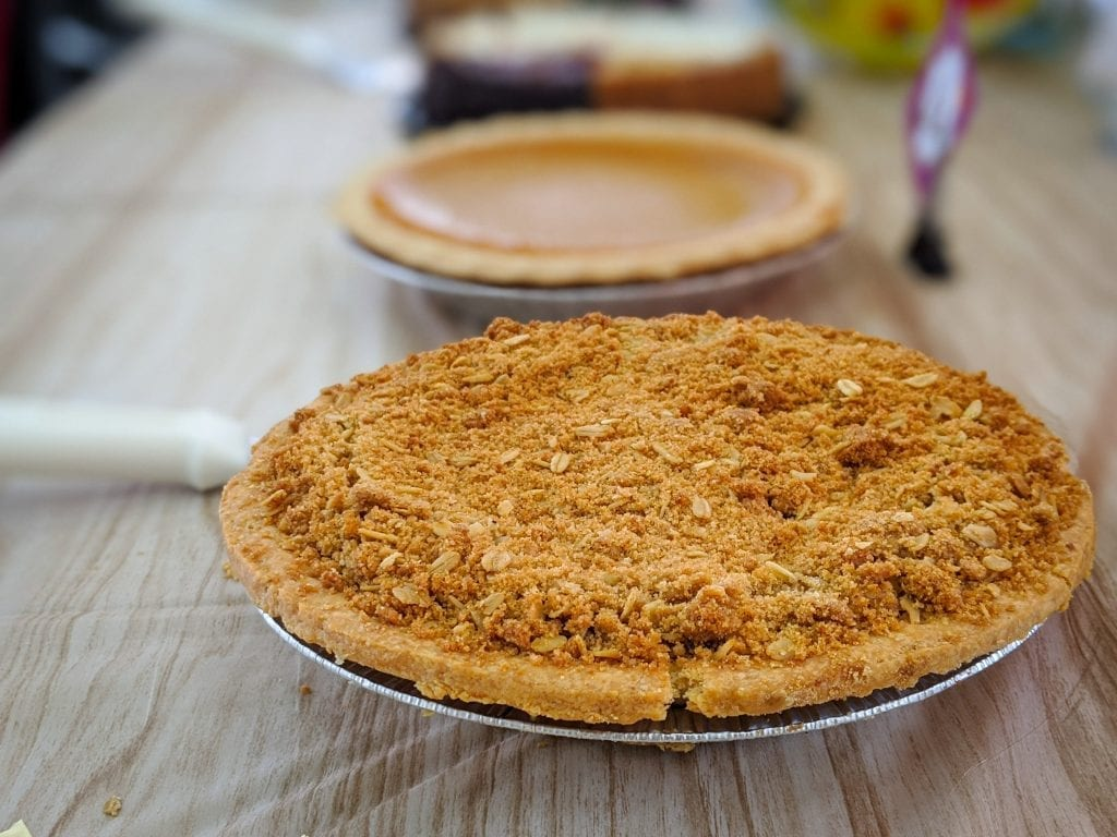 Edible apple pie on a wooden table with pumpkin pie and other types of pie in the background