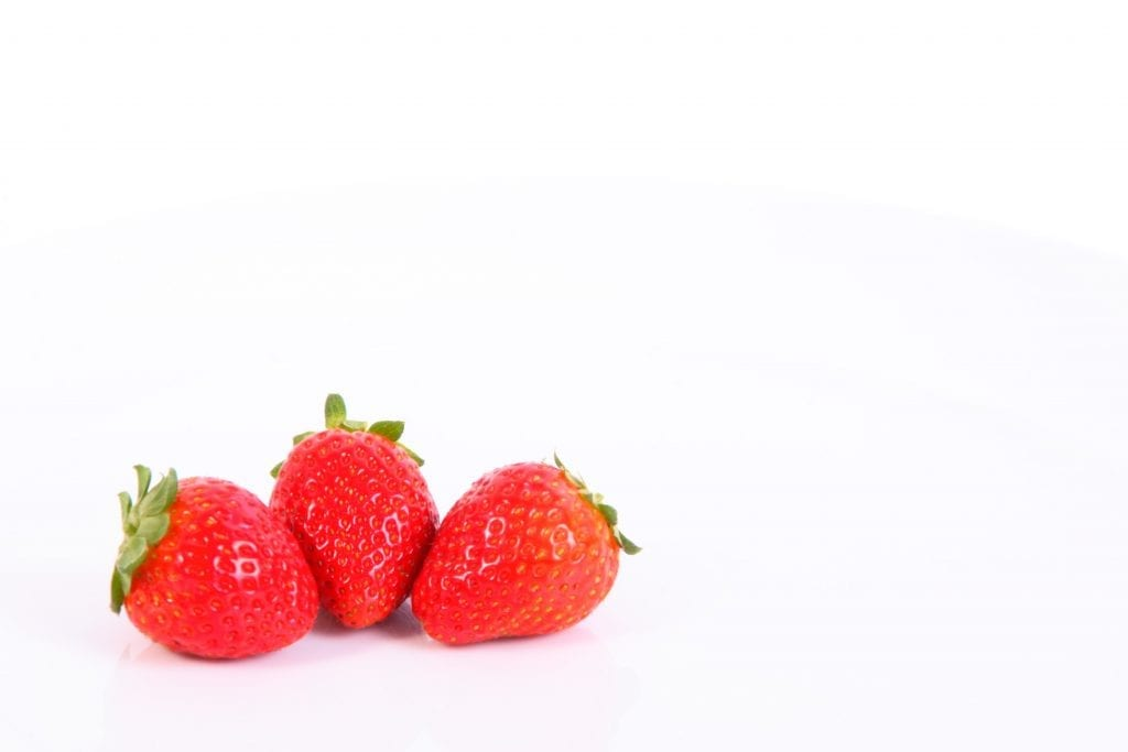Three strawberries bright red on a white table shot in macro