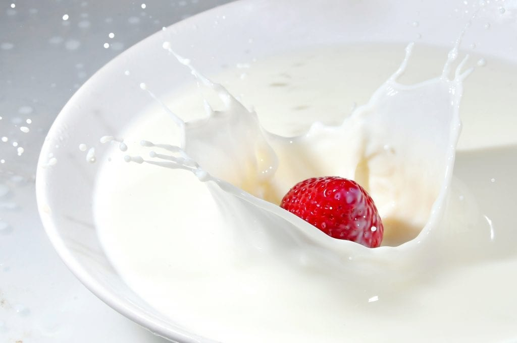 Strawberry being dropped into a glass of milk