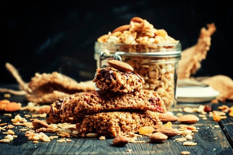 Cannabis infused cereal bars on a wooden table with a glass dish in the background that has more cereal bars in it