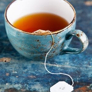 Edible tea in a blue tea cup on a blue counter surface.
