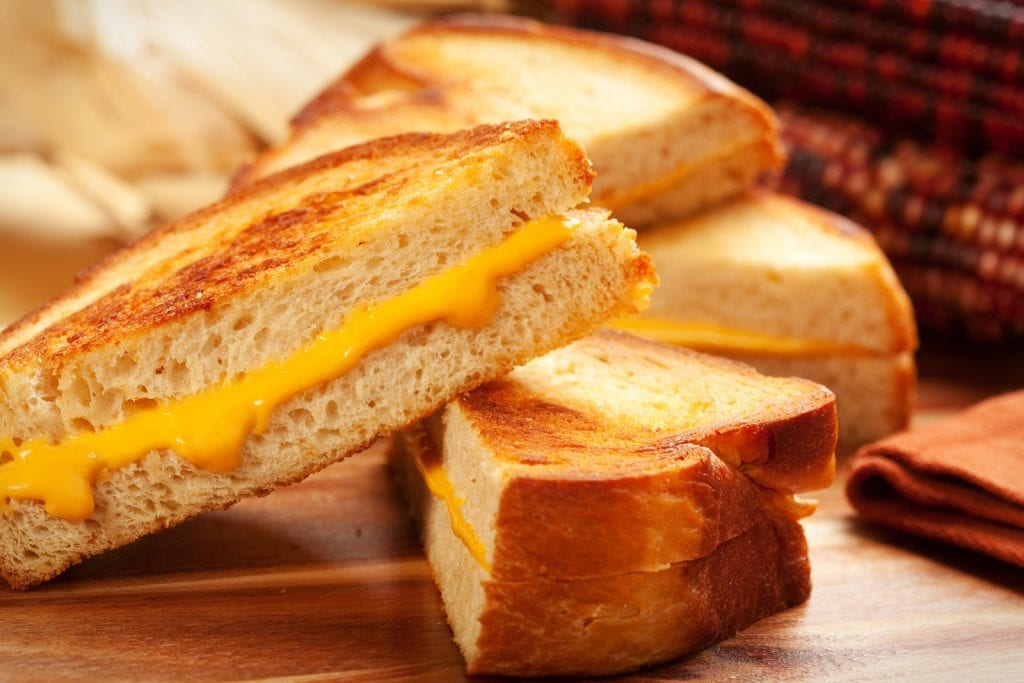 Macro of cannabis infused grill cheese on a wooden surface with more grilled cheese in the background