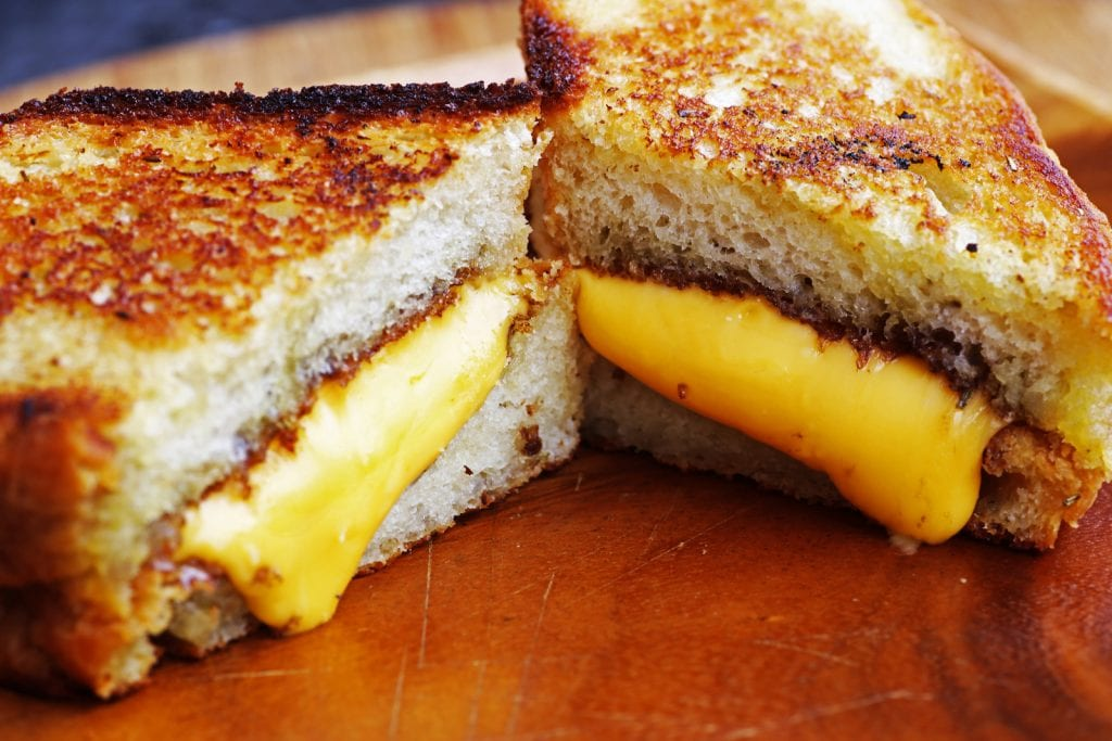 weed Grilled cheese sandwich on wood platter with rosemary bread & melted cheddar cheese