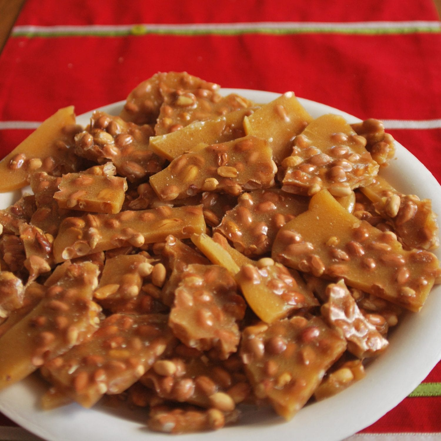 cannabis infused peanut brittle on a white plate which is all on a red tablecloth