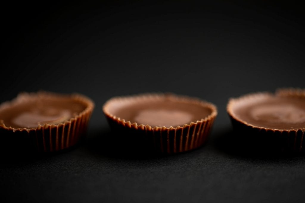 3 weed peanut butter cups on a dark black background macro