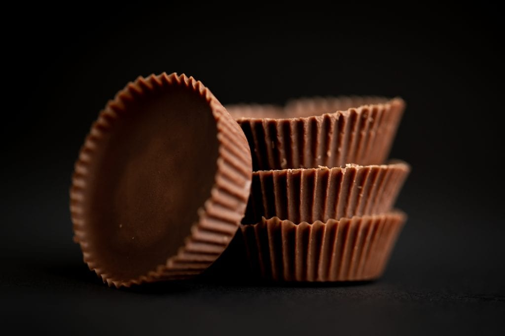 a stack of cannabis infused peanut butter cups with one cup leaning against the stack. All of this is on a black background shot in macro