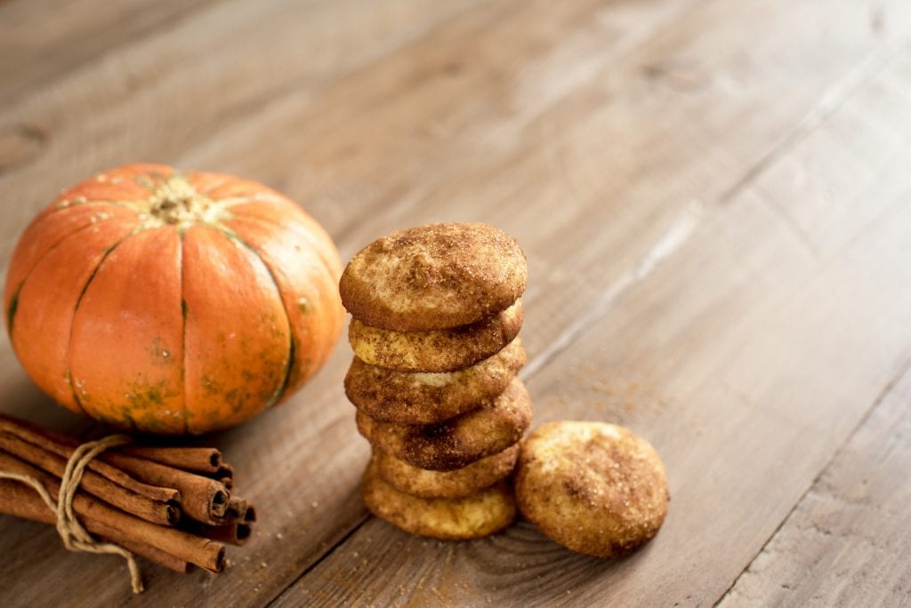A stack of cannabis infused snickerdoodle cookies on a wooden surface with a pumpkin and cinnamon sticks in the background