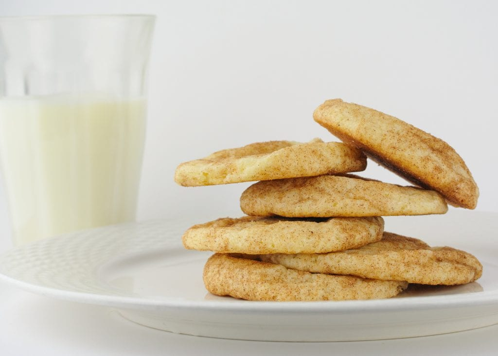 This photo depicts an uneven stack of weed snickerdoodle cookies. A glass of organic milk sits behind the white plate of cookies. Both the milk and the dessert are in front of a white background.
