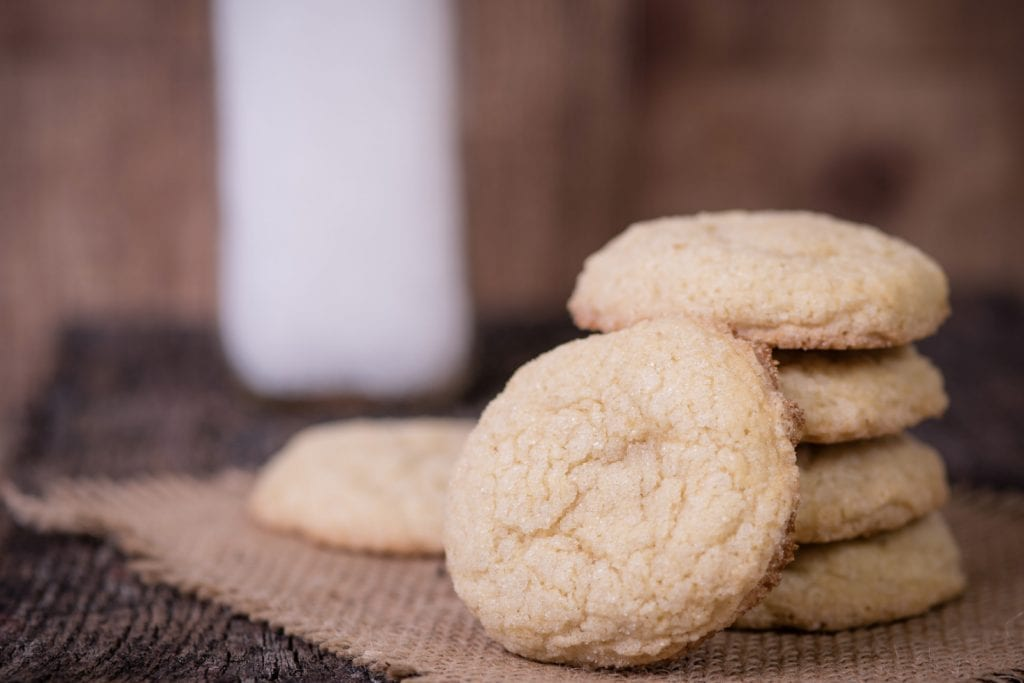 a stack of weed sugar cookies on a rustic wooden surface with more sugar cookies around the stack