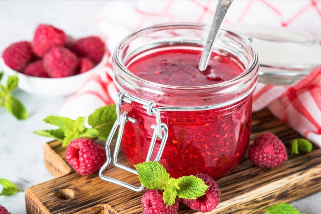 macro of weed jam in a glass jar on a wooden cutting board with a spoon in the jar and raspberries in the background