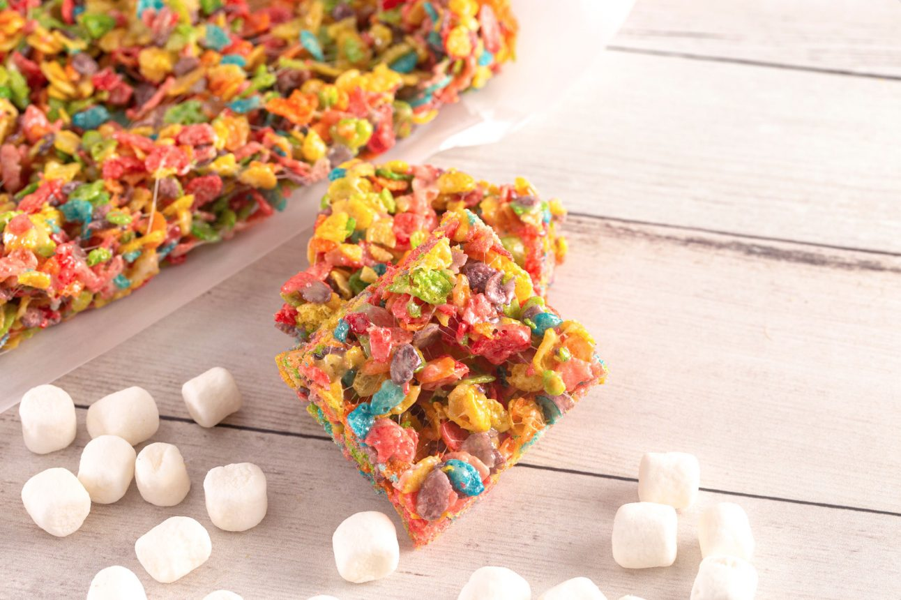 overhead shot of cannabis infused fruity pebble bars on a wooden table with marshmallows spread around the bars