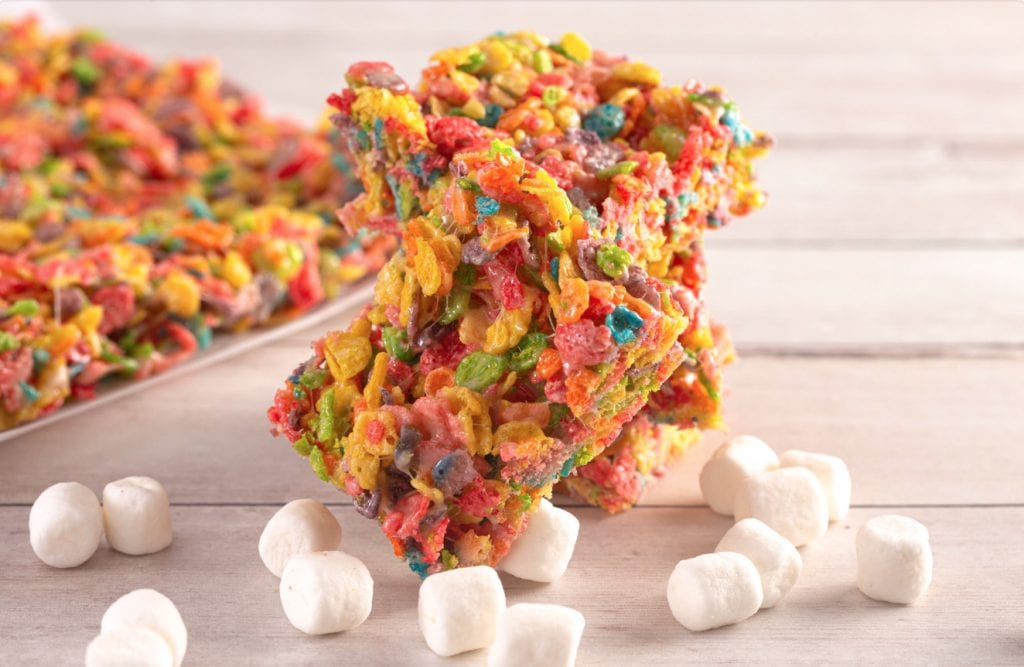 Two cannabis infused fruity pebble cereal bars on a wooden table with marshmallows scattered around on the wood surface. More cereal bars in the background