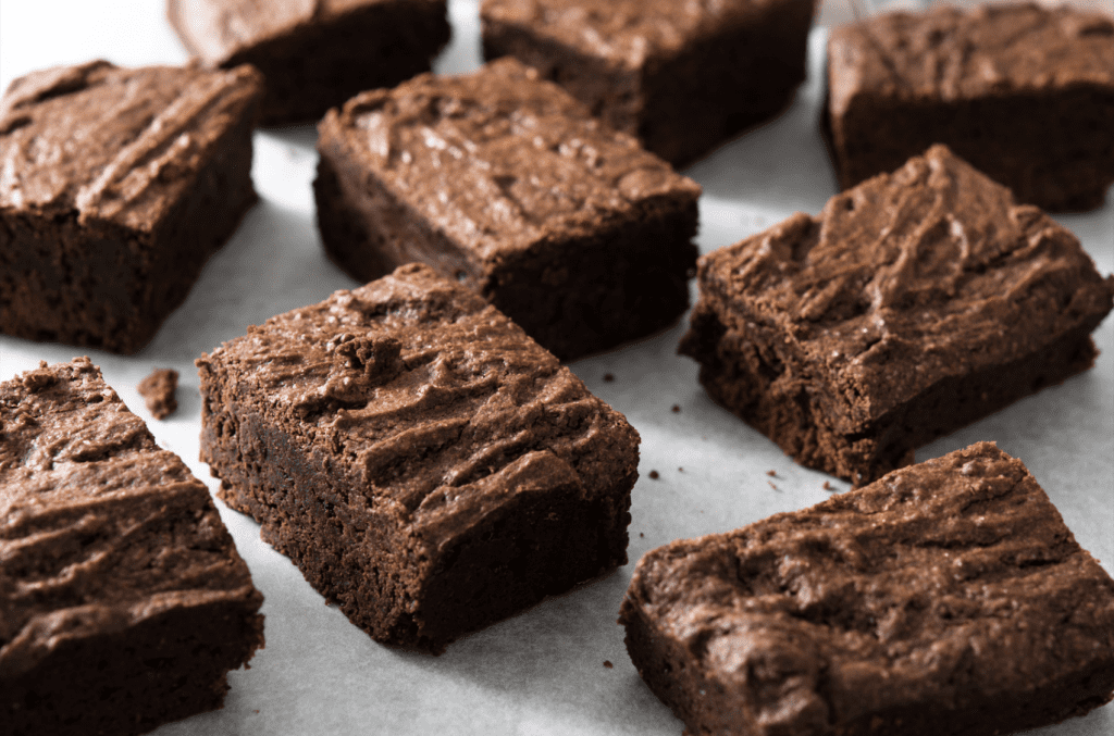 weed brownies cut up into nine separate slices laying ontop of a piece of parchment paper. The pot brownies are spread around on the parchment paper artistically.