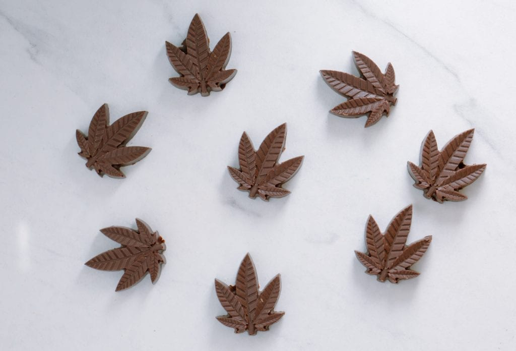 cannabis leaf shaped chocolates on a white marble counter.