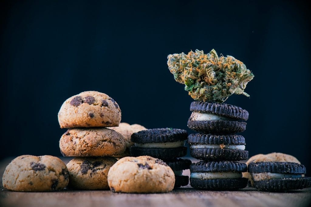 Cannabis nug on top of infused oreo cookies and chocolate cookies on a wooden table.