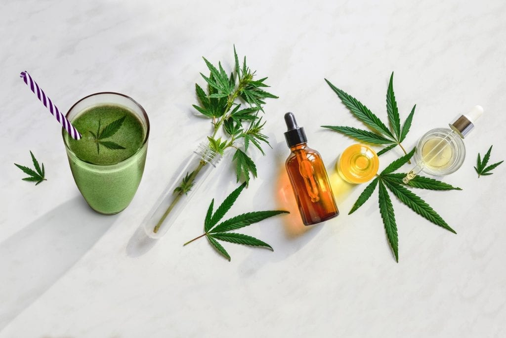 cannabis oils spread out on a marble table with a weed smoothie on the side of the counter.