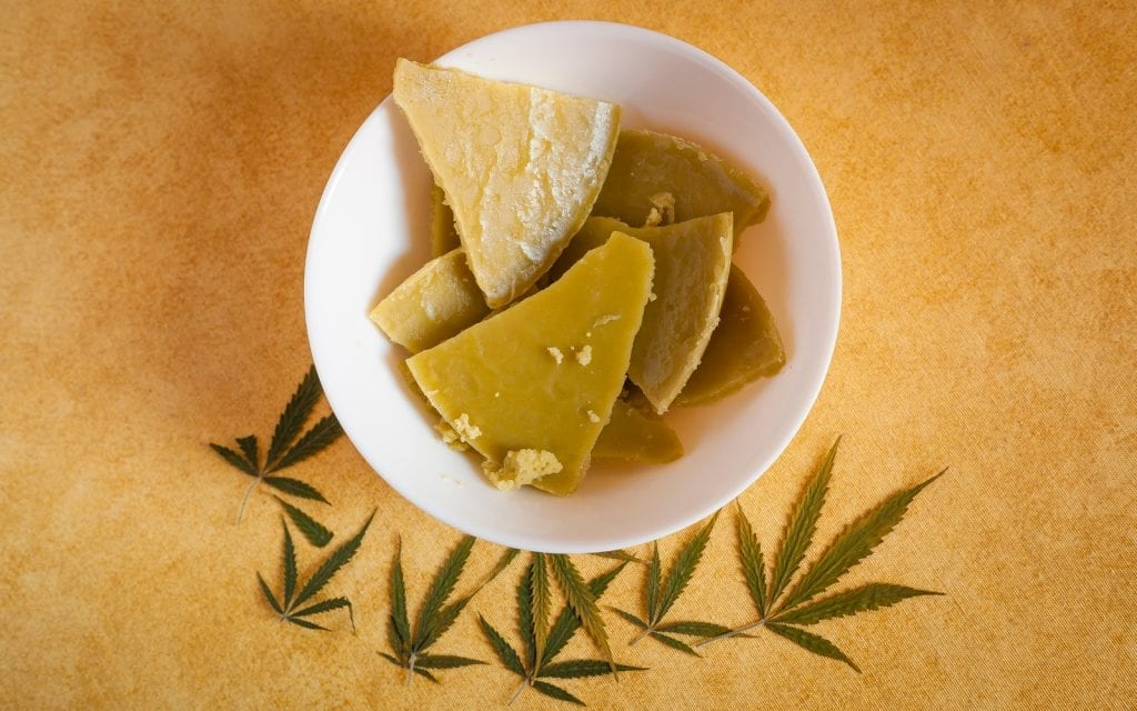 Fresh made cannabis butter on a bowl with some marihuana leaves. Cannabis cannae may be used with recreational or medical purposes. Edible cannabis concept.A cannabis edible, also known as a cannabis-infused food or simply an edible, is a food product that contains cannabinoids, especially tetrahydrocannabinol. Cannabis-infused butter, or cannabutter, is a cannabis-infused ingredient used in many cannabis edibles. Heating the raw cannabis in melted butter allows the cannabinoids to be extracted by the fat. Used to make weed christmas cookies