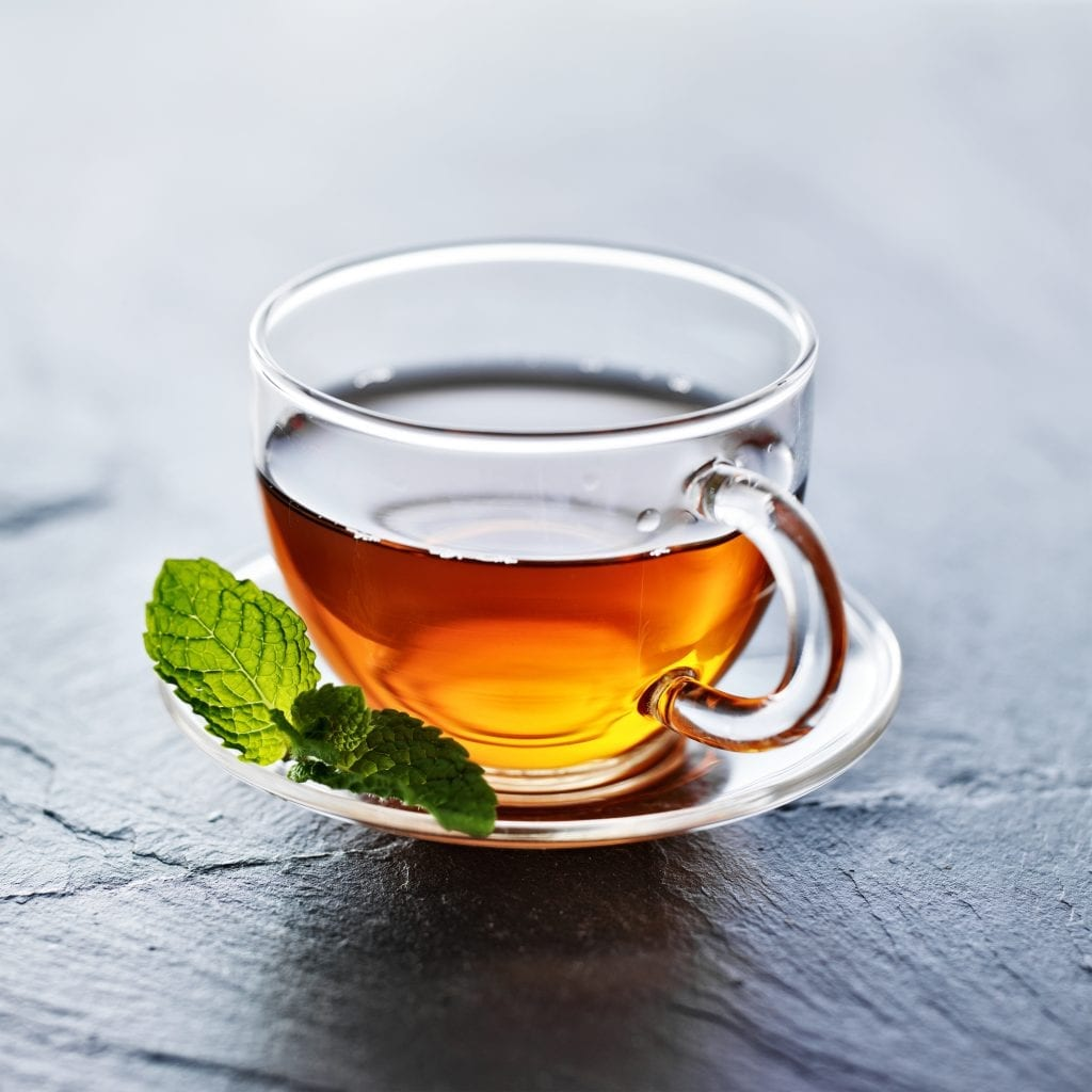 glass of hot tea with mint garnish on a white plate used for at home remedies