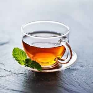 glass of hot weed tea with mint garnish