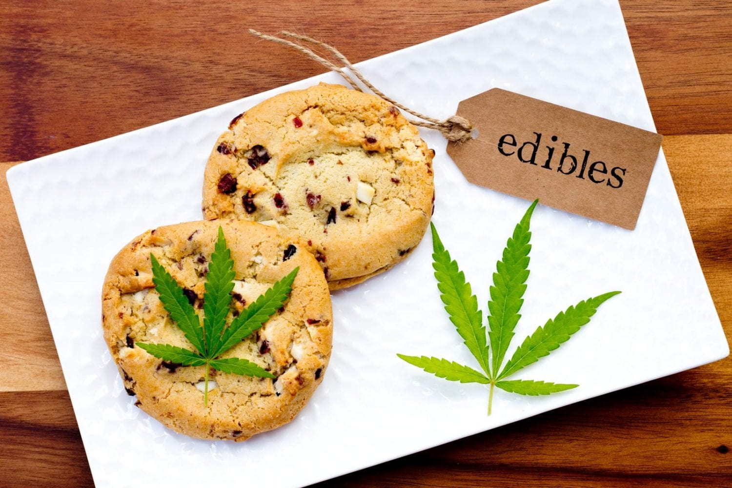 """two weed edible cookies on a napkin with a tag that has """"edible"""" written on it"""