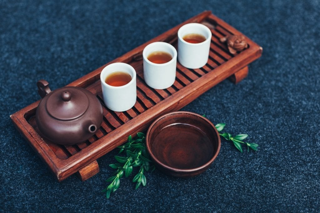 A kettle with three mugs of CBD tea sitting on a wooden board. There is a wooden bowl also filled the infused tea that sits in front of the kettle.
