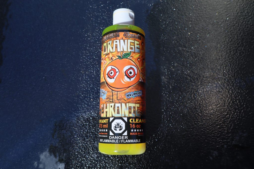 orange chronic glass cleaning solution. The plastic bottle sits on a glass surface.