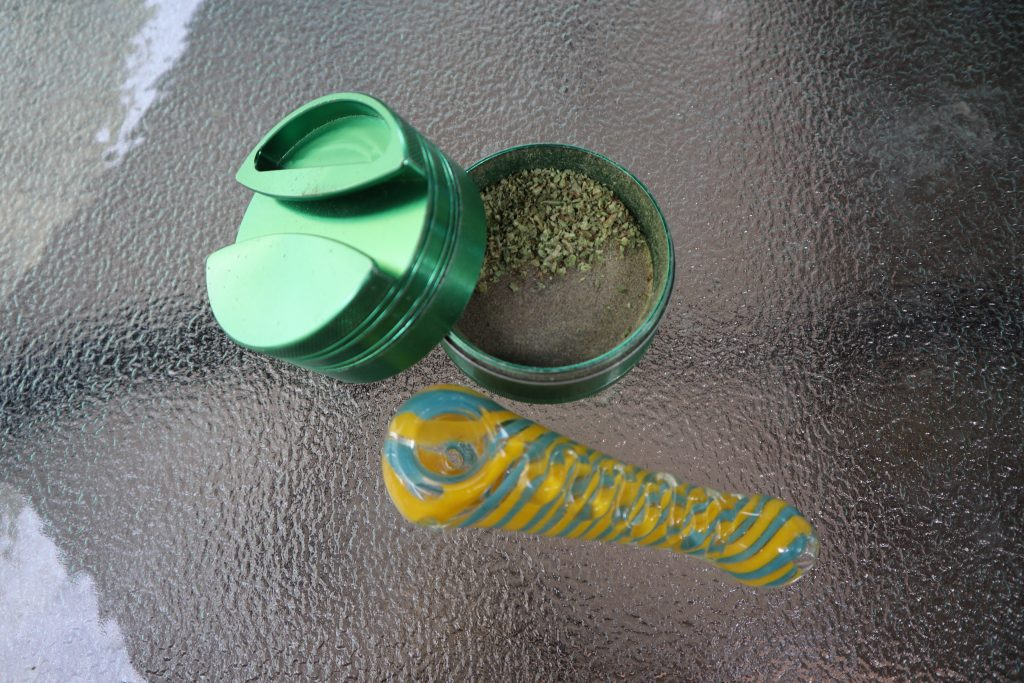 A green grinder and glass weed pipe on a glass table.