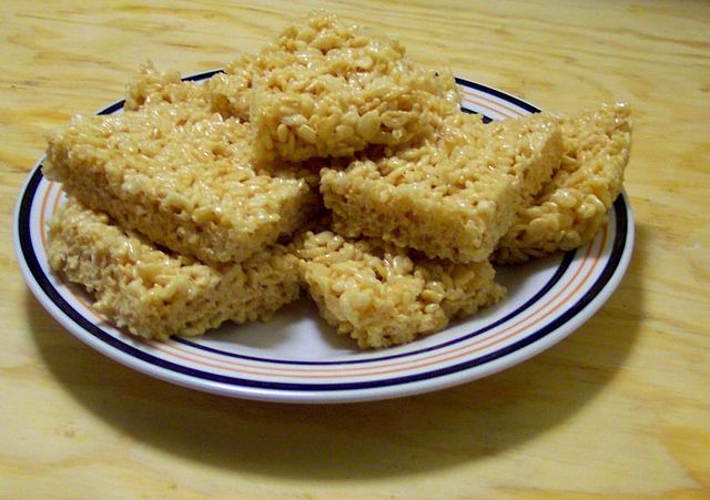 cannabis-infused vegan rice krispies treats cut into individual portions on a white plate. The plate sits on top of a wooden table.