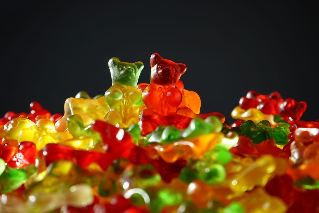 CBD infused gummy bears sit in a big pile on top of each other. The gummy bears are red, yellow, and green in color.