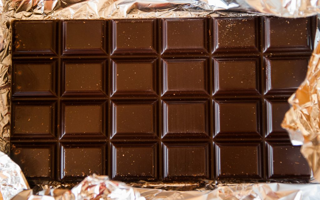 CBD chocolate bar in a tinfoil wrapper. The chocolate bar is divided into 24 portions.
