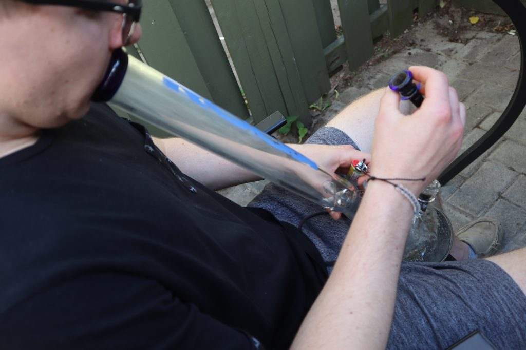 An individual inhaling from a water pipe. The water pipe is glass and has blue writing on the side.