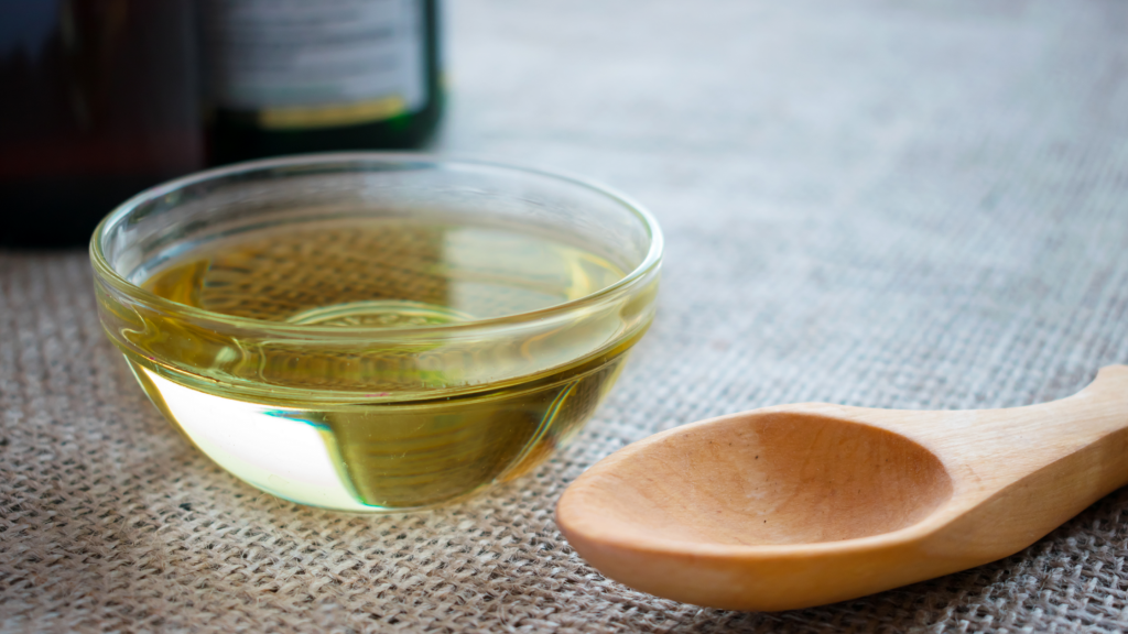 CBD MCT oil in a glass bowl on top of a counter with fabric covering it. A wooden spoon sits beside it on the right of the bowl.
