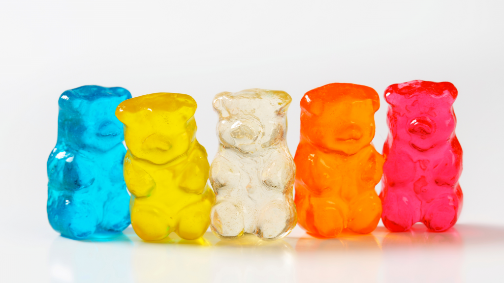 cbd gummy bears sitting beside one another. There is five gummy bears in total. A blue, yellow, clear, orange, and pink one.