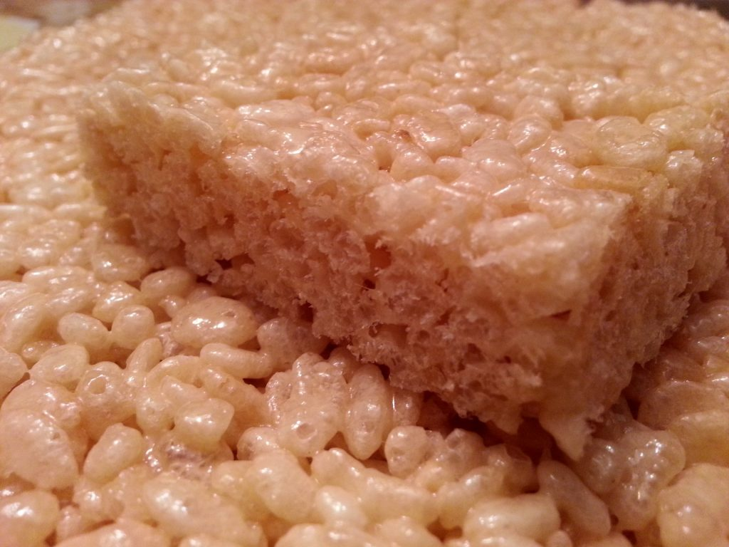 CBD rice krispies treats cut into square portion/ The small grains of rice krispies cereal stick together.