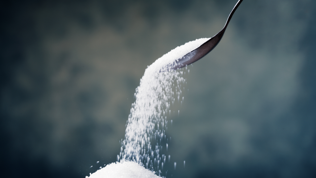 CBD-infused sugar falling off of a metal spoon. The small grains of white sugar make a pile.