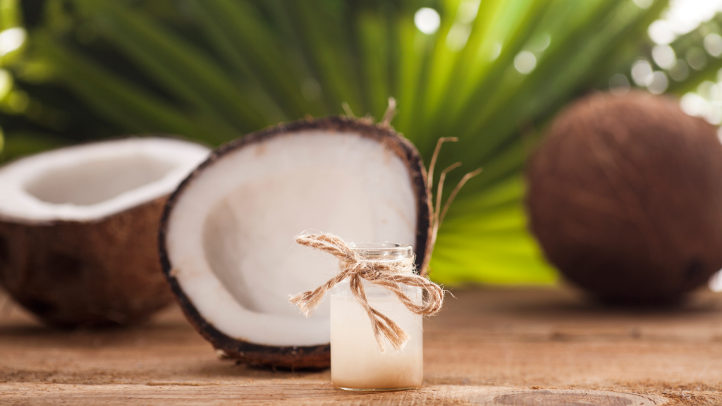 A glass jar filled with coconut oil sits on a wooden surface. Behind the jar there is coconuts that have been broken open.
