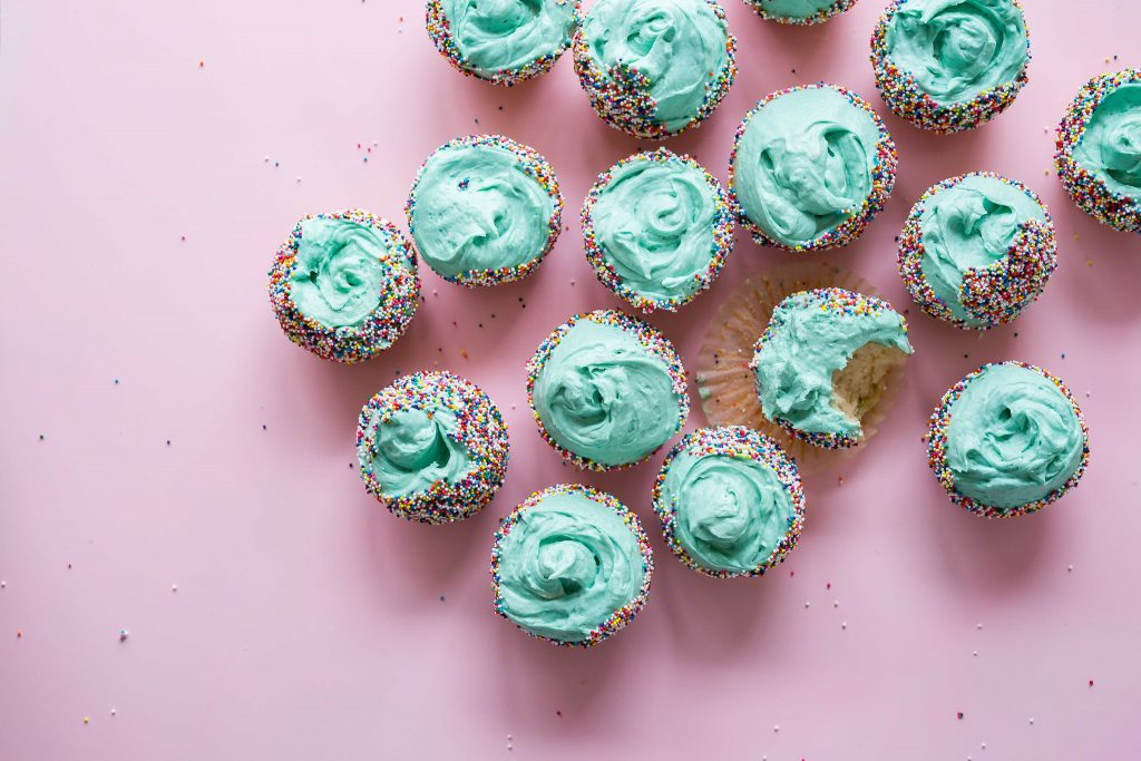 Gluten free weed cupcakes with light blue icing and rainbow sprinkles. The 16 cupcakes sit on a pink surface.