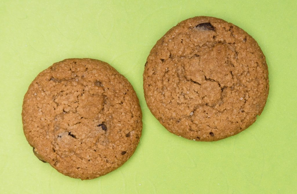 gluten free weed cookies sitting on a green surface. The two cookies sit next to one another.