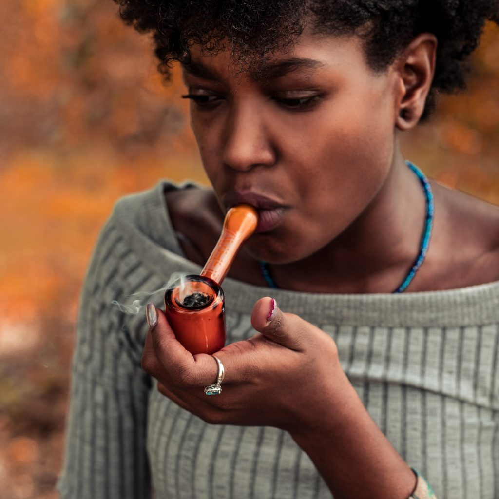 a woman holding an orange pipe to her mouth. She is wearing a grey sweater.