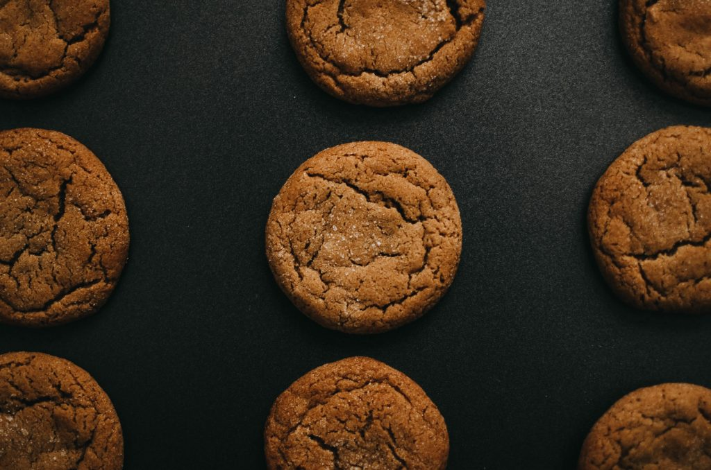 gluten free peanut butter weed cookies spread out evenly on a black surface.