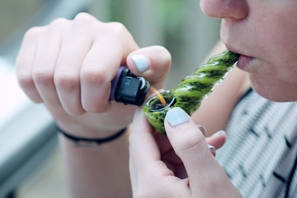 a woman holding a pipe igniting a bowl of cannabis.