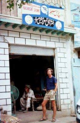 a tourist at a hashish store in pakistan, europe. The man stands in front of the door way.