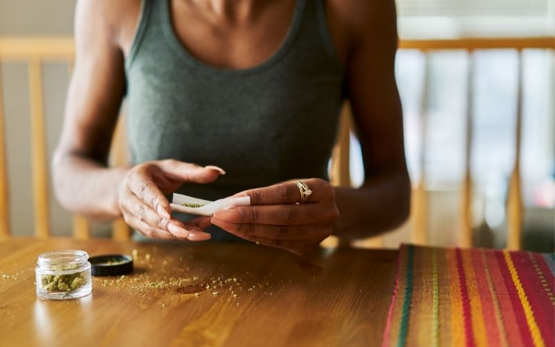 Woman rolling a joint on a wooden table with a grinder beside her