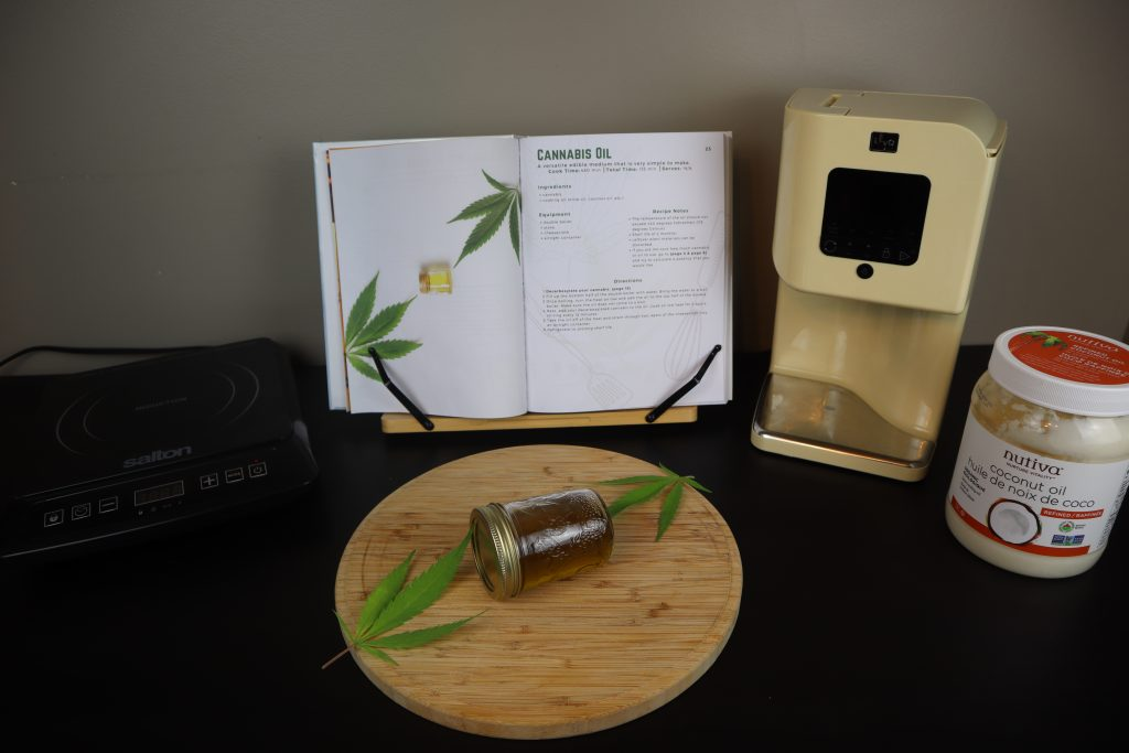 Cannabis coconut oil in a mason jar with cannabis leafs beside it on a wooden cutting board. A induction cooker, cannabis cookbook, levo infusion machine, and coconut oil are behind it on a black table.