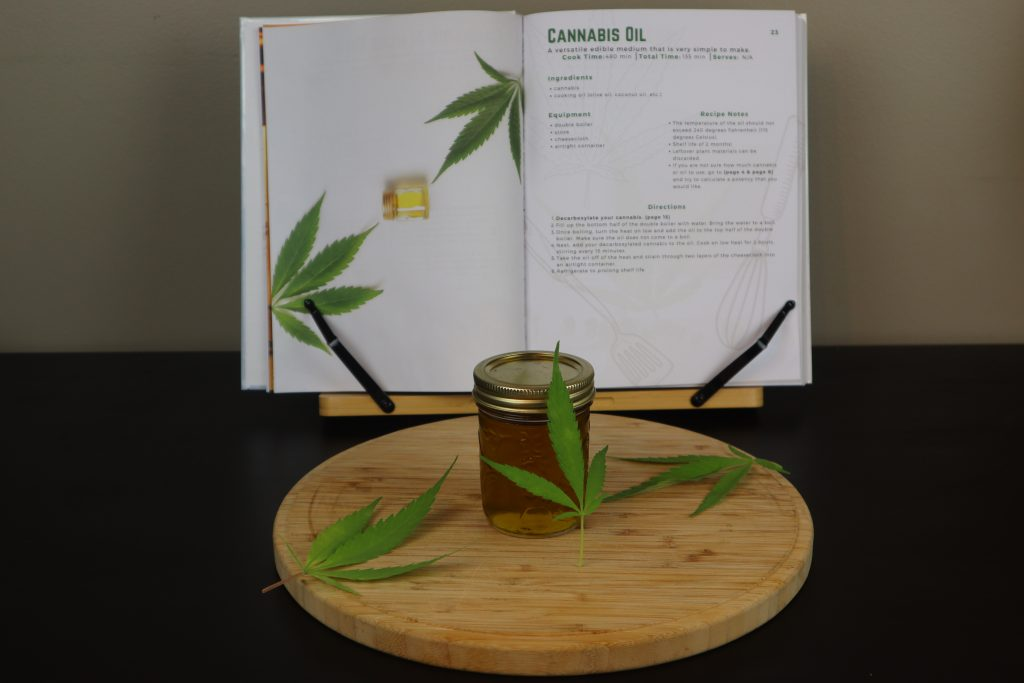 Cannabis oil in a glass mason jar with cannabis leafs laying beside it. A cannabis cookbook is behind the cutting board on a black table.