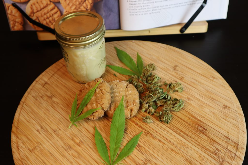vegan weed peanut butter cookies on a cutting board with cannabis coconut oil, cannabis buds, and cannabis leafs beside it. A cannabis cookbook is in the background.